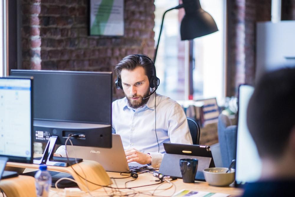 man wearing headphones in front of computer