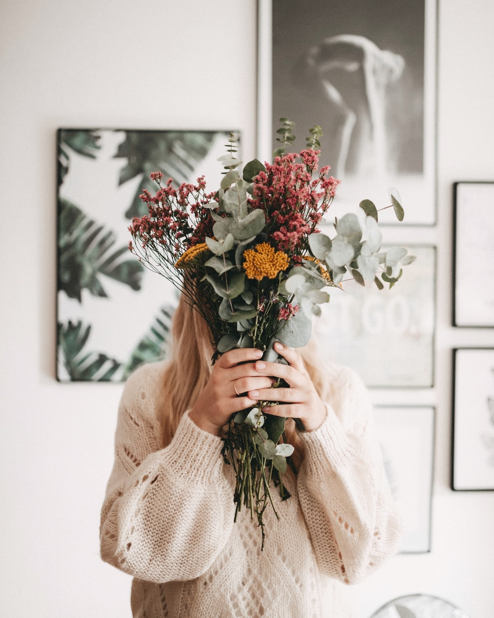 woman hiding her face using bouquet