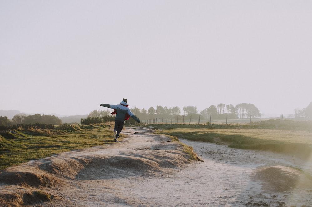 person wearing jacket running on grass field