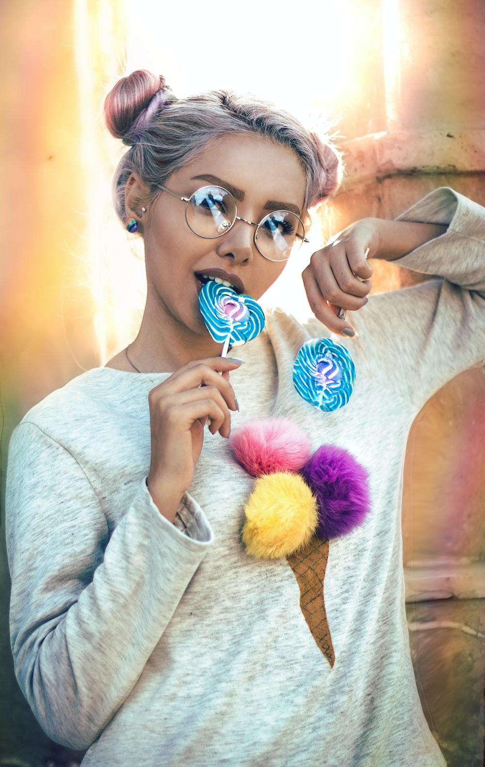 woman eating heart shape swirl lollipop
