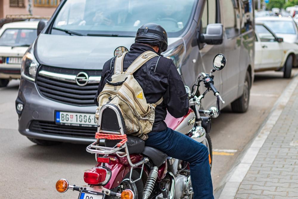 man riding motorcycle in road during daytime