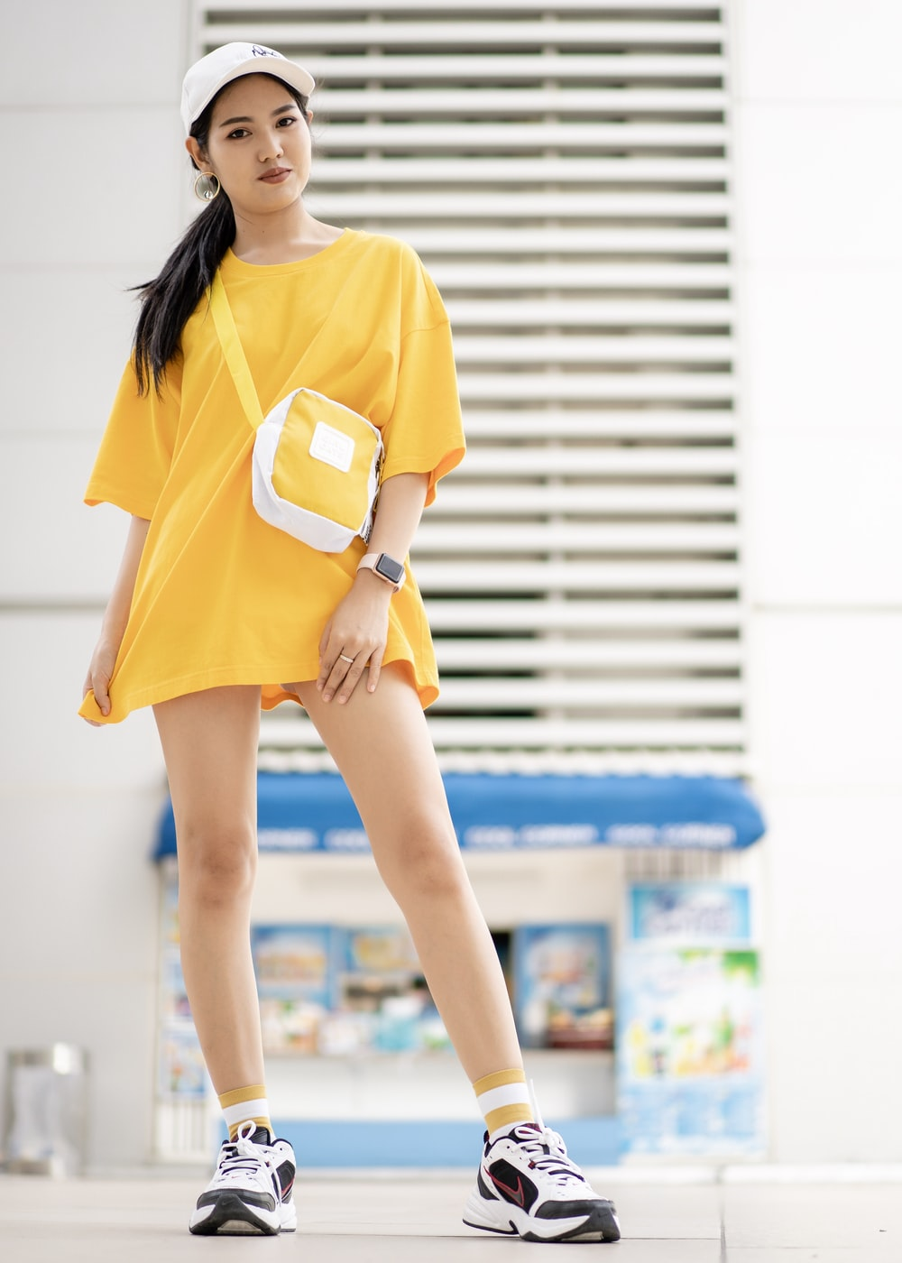 woman wearing yellow crew-neck shirt and yellow and white sling bag