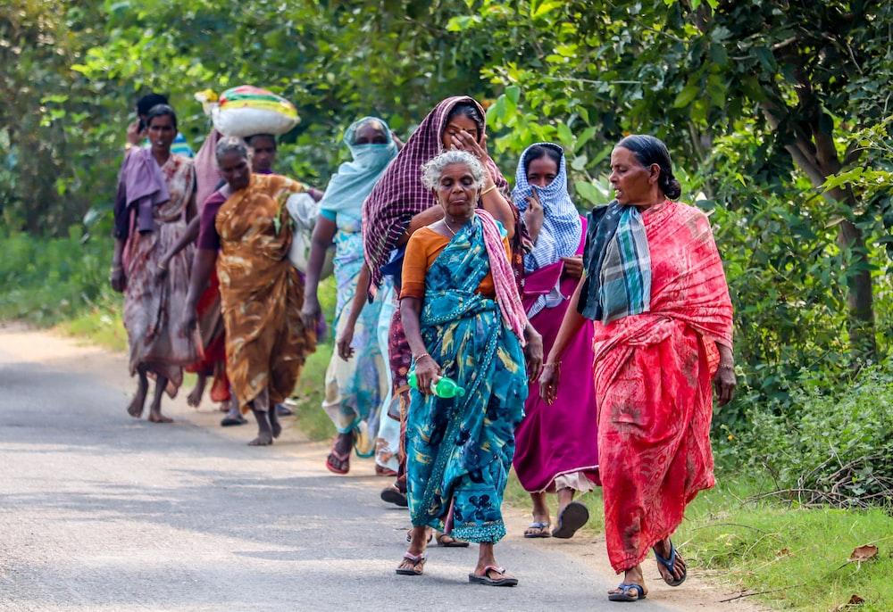group of women wearing saree dress walking beside trees