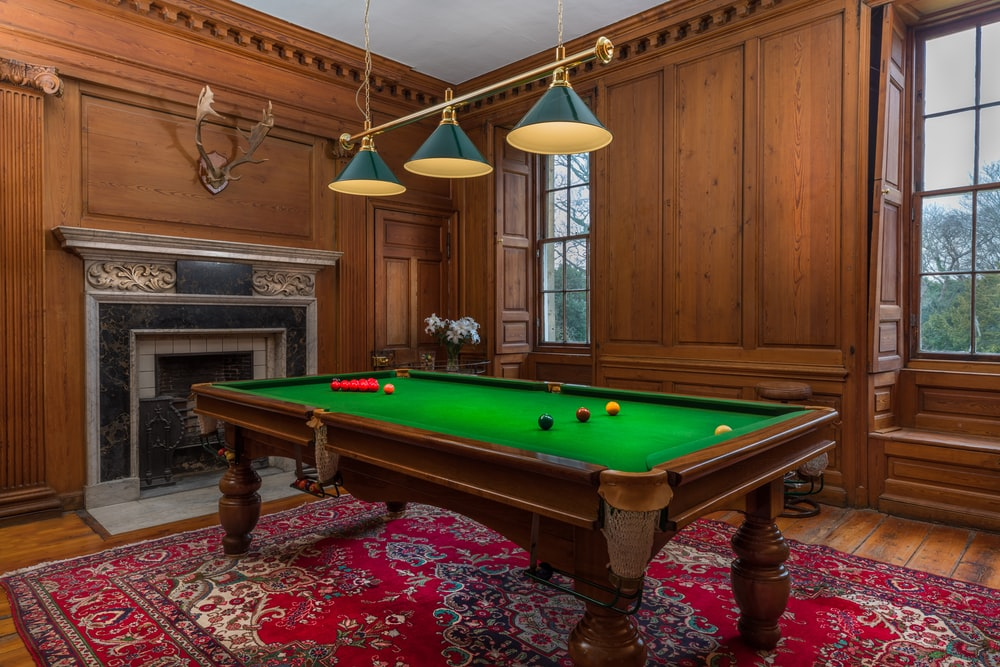 brown and green billiard table near fireplace