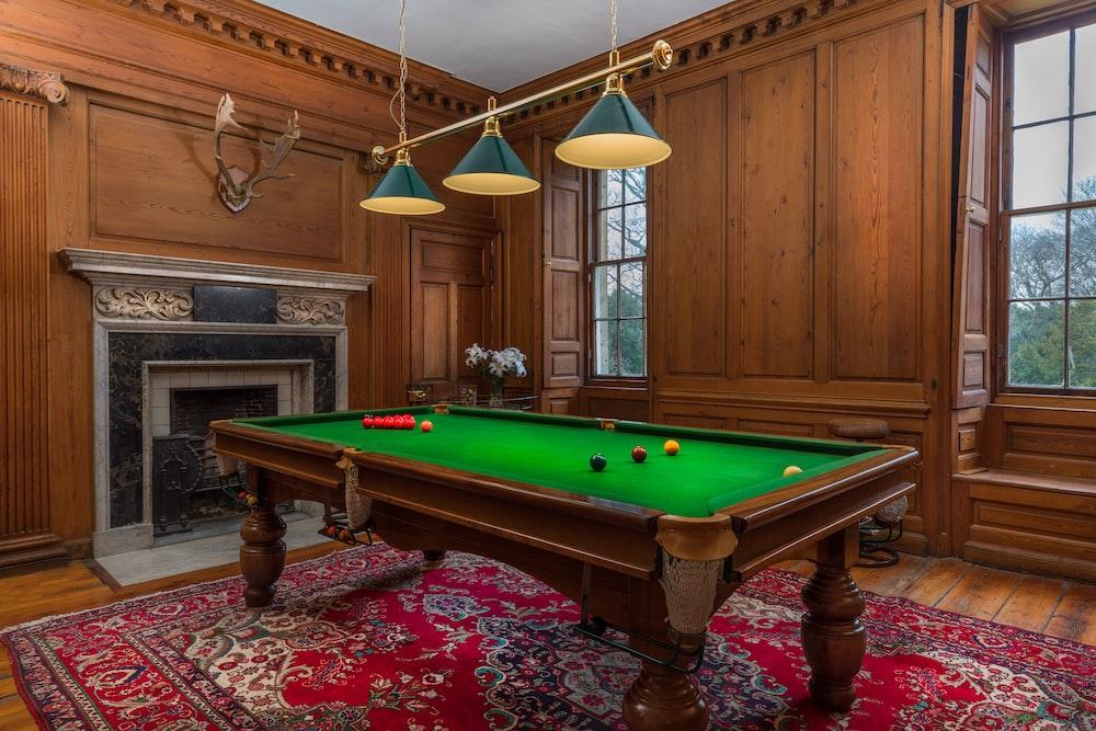 brown and green billiard table near fireplace