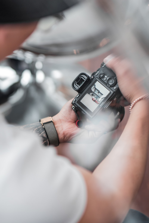 person holding black digital camera