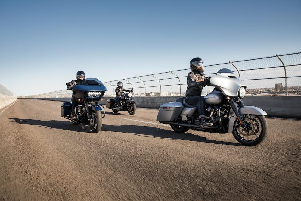 three men riding touring motorcycles