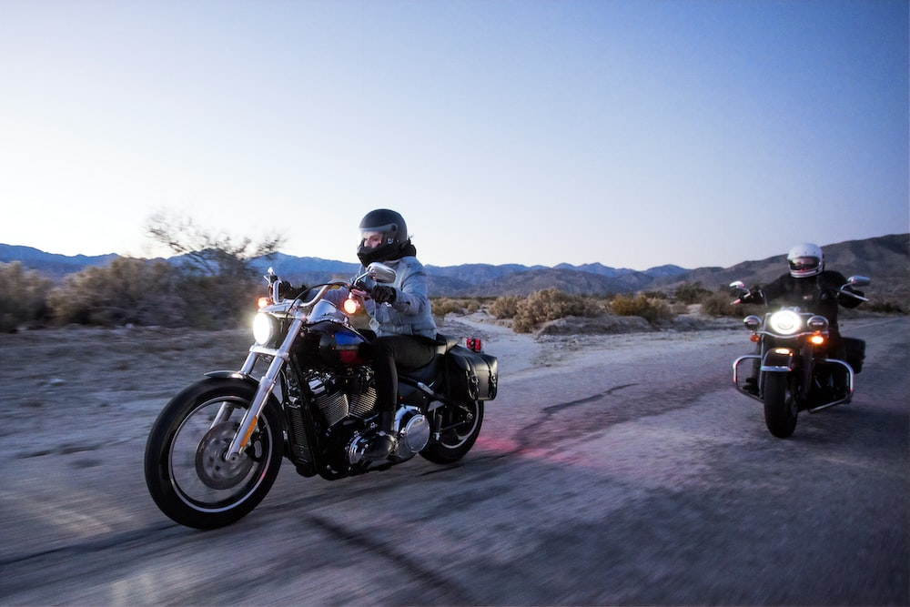two persons riding motorcycles