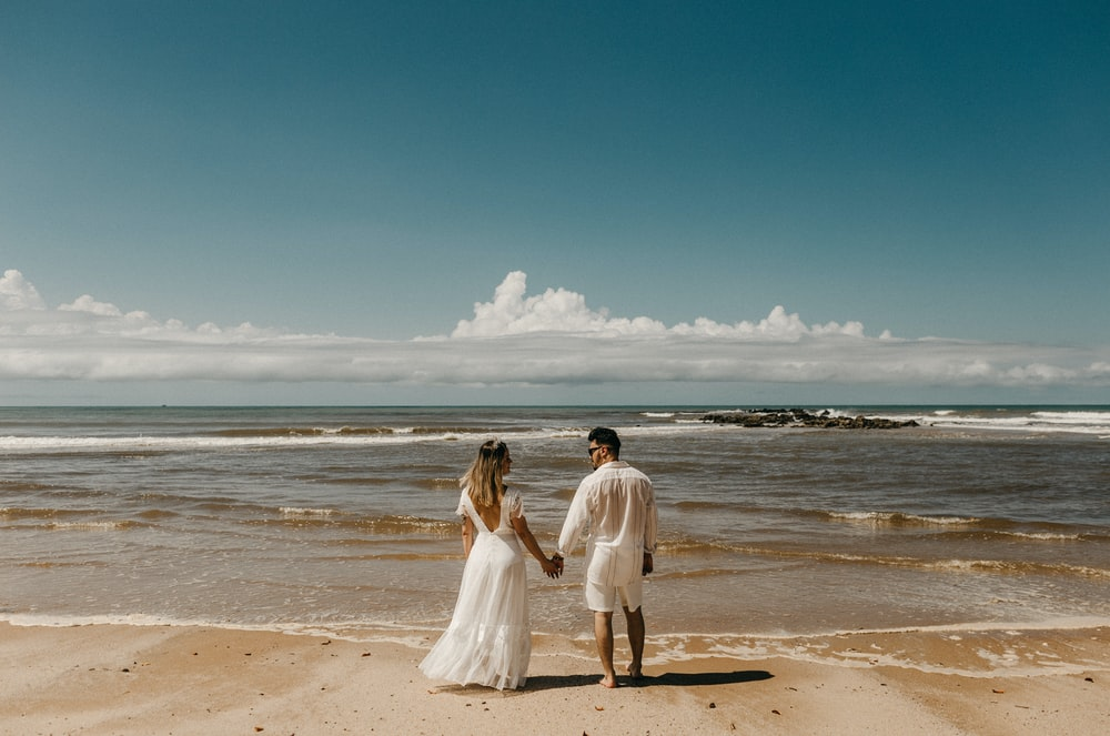 woman and man standing in front of shoreline