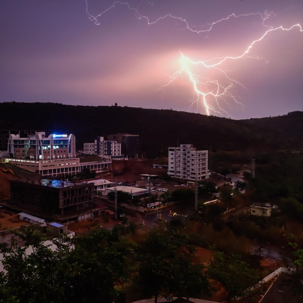 lightning on mountain near buildings