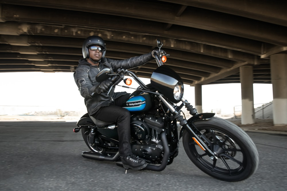 man riding black motorcycle