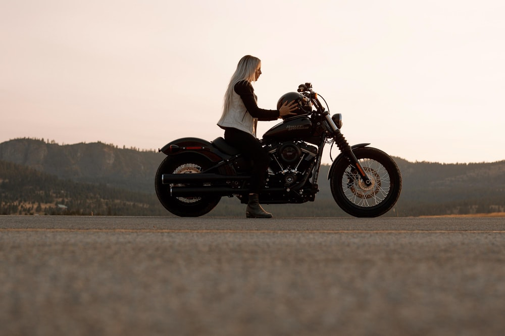 woman sitting on black and gray cruiser motorcycle
