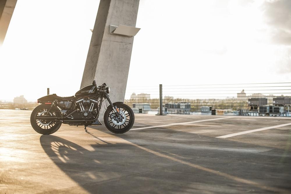 black motorcycle parked near grey concrete pillar