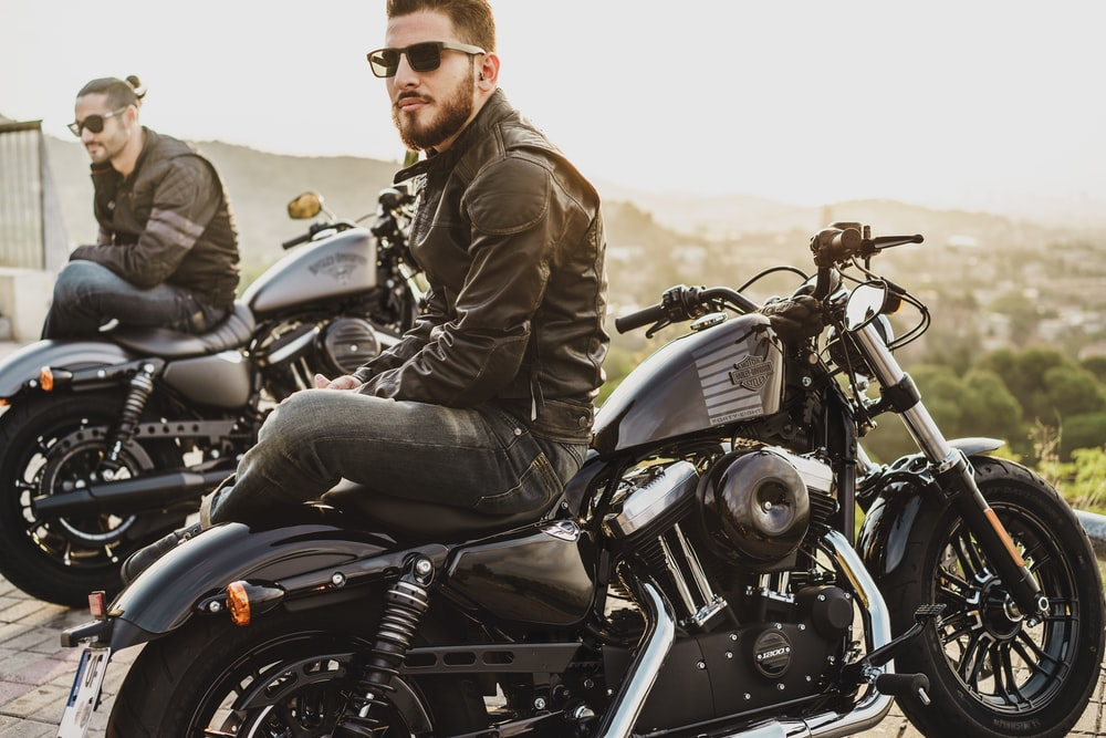 two men sitting on two parked cruiser motorcycles