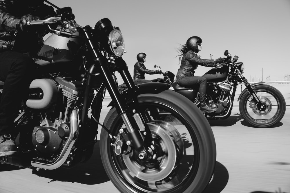 black and white photo of people riding motorcycle