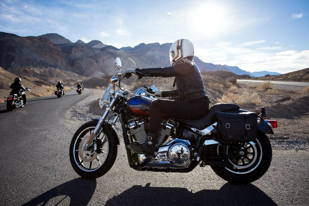 man riding touring motorcycle during daytime