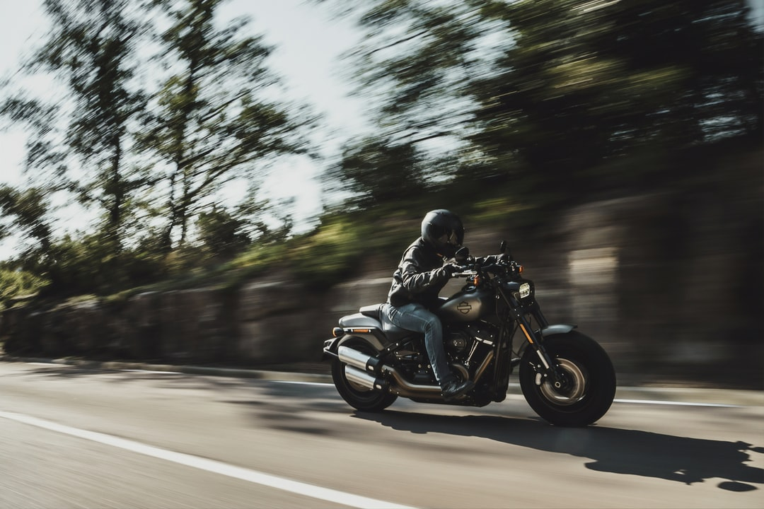 motorcycle rider wearing a helmet driving at a fast rate of speed