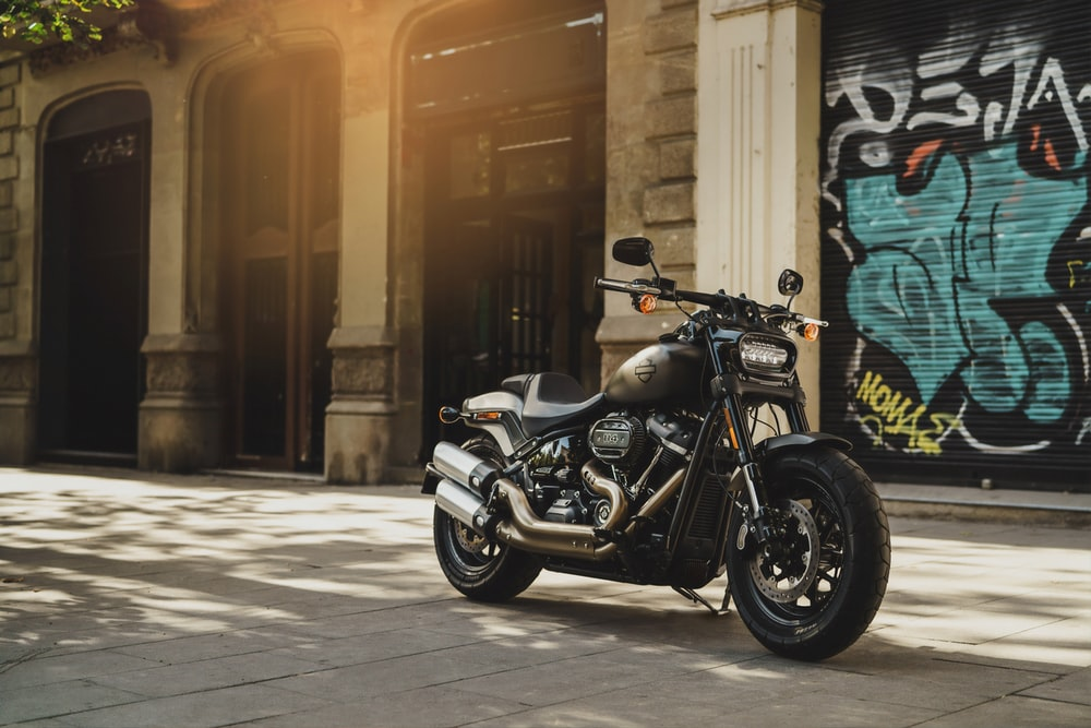 black motorcycle near wall with grafitti