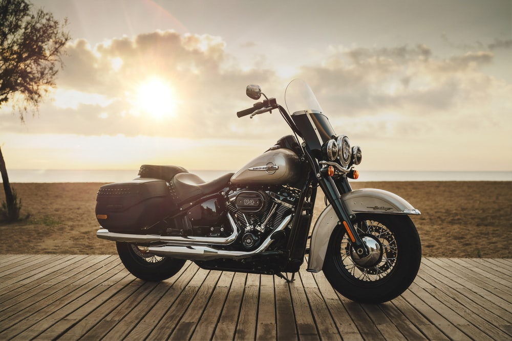 black and gray touring motorcycle on wooden dock near brown field under gray and orange skies