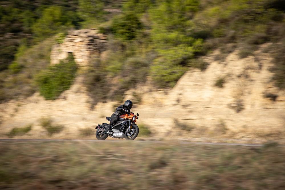 man wearing helmet riding motorcycle near cliff