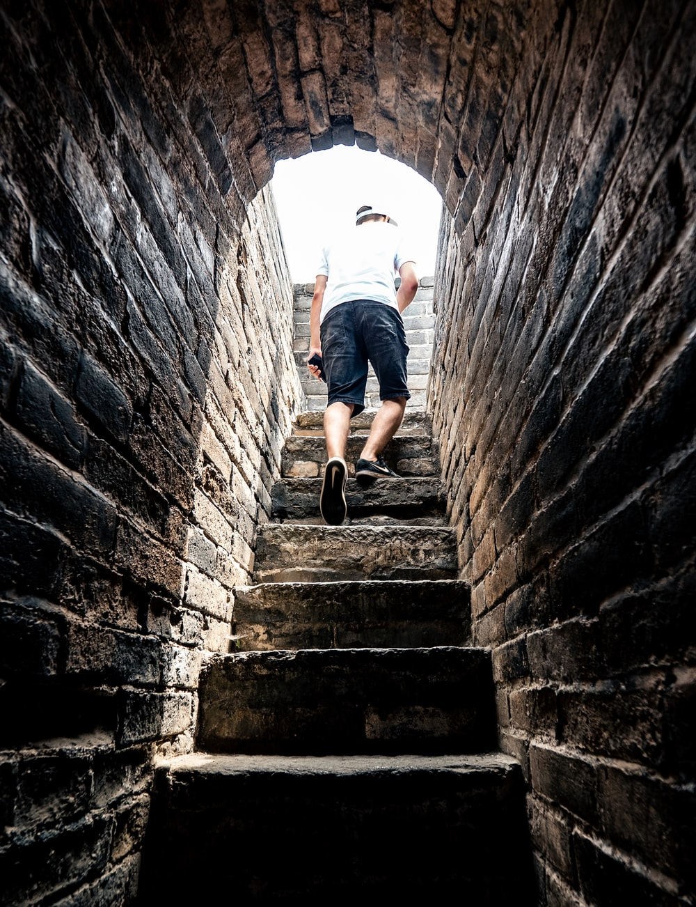 person in white t-shirt and black shorts walking outside of tunnel