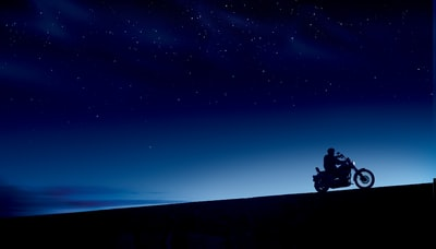 person riding motorcycle under blue and black skies during night time