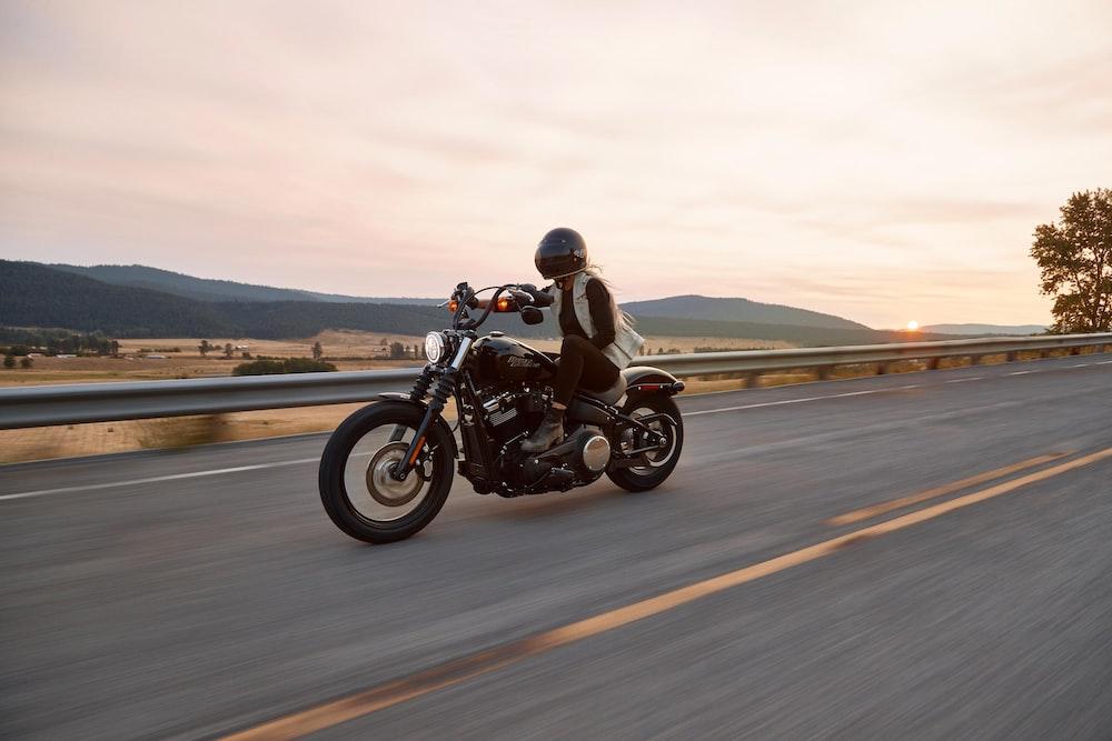 man on black cruiser motorcycle in highway