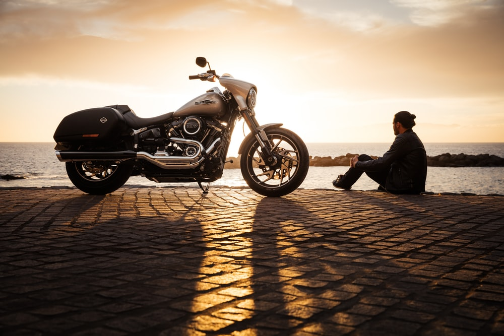 man sitting on ground beside parked silver cruiser motorcycle
