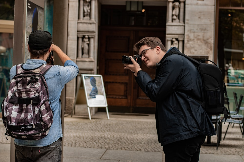 man in black jacket taking picture of man in blue denim jacket
