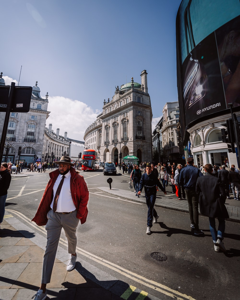 man in white dress shirt and red jacket crossing street