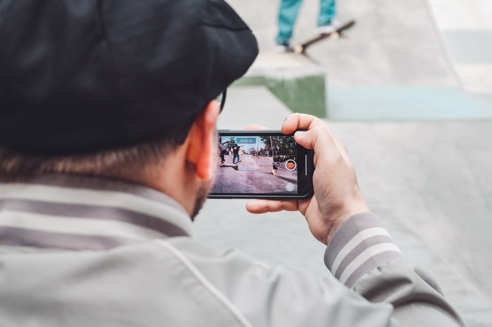 person taking photo frame phone