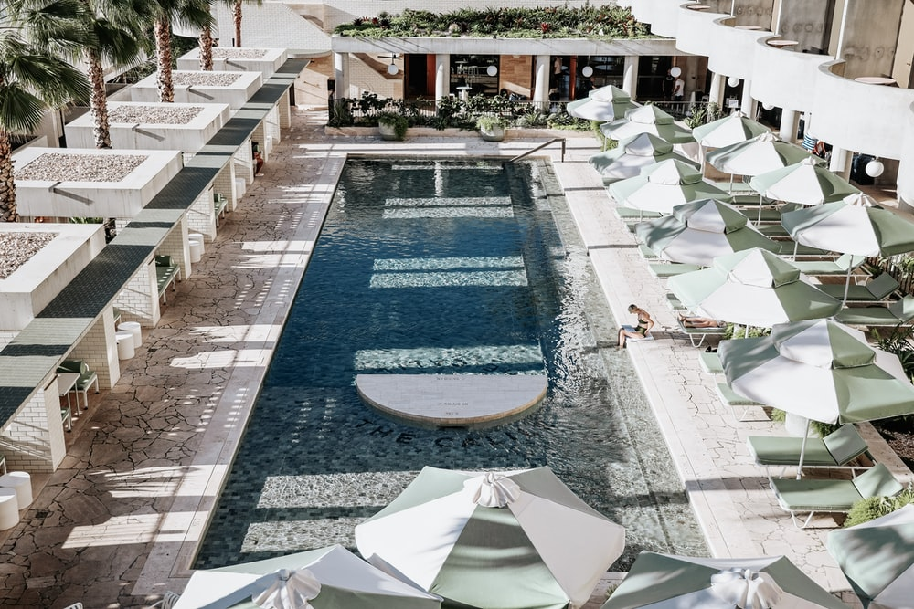 rectangular swimming pool surrounded with umbrellas