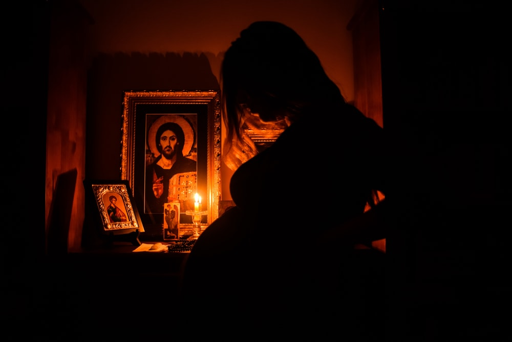 silhouette of pregnant woman beside religious altar