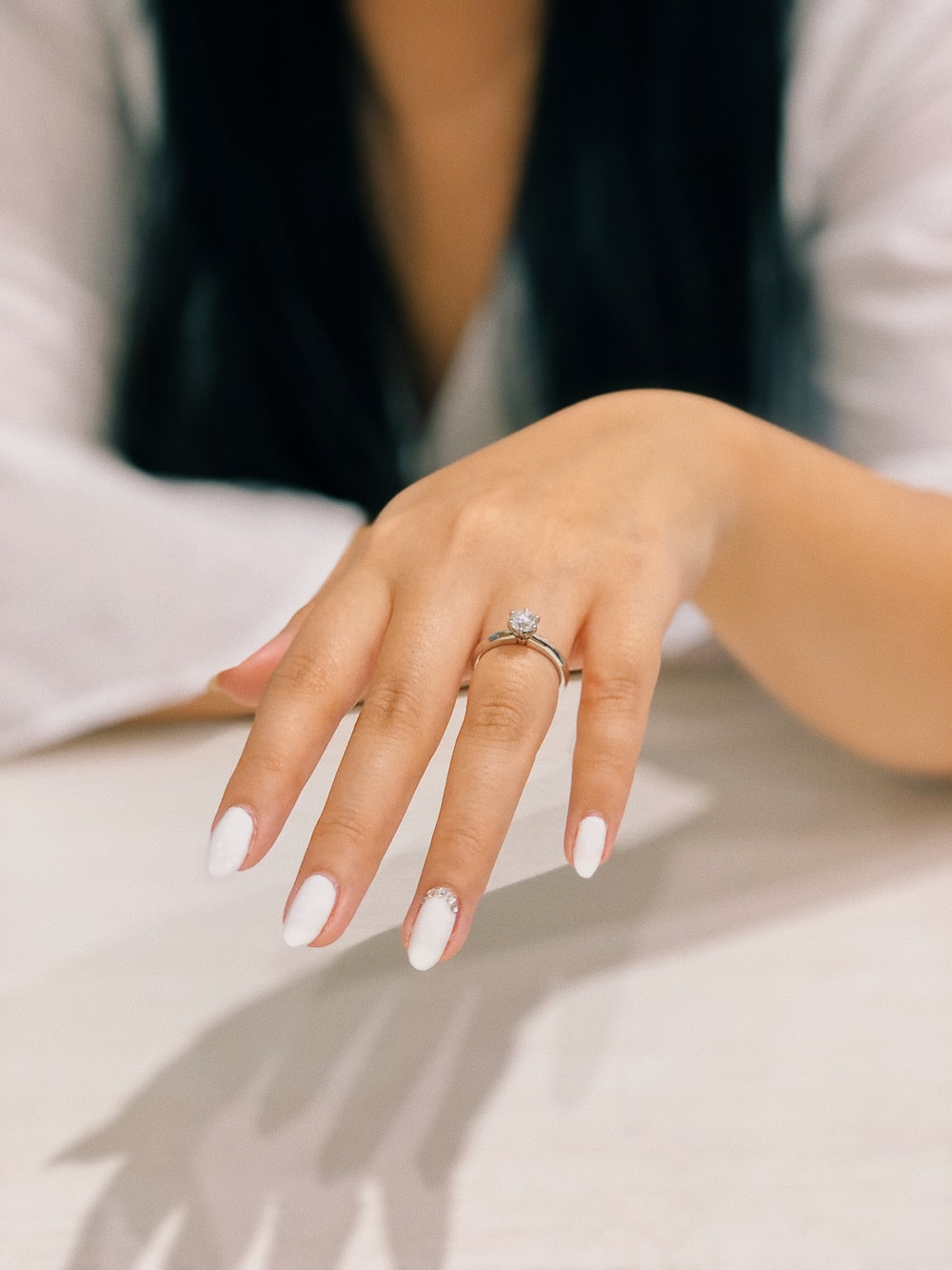 person with white nail polish on left fingers
