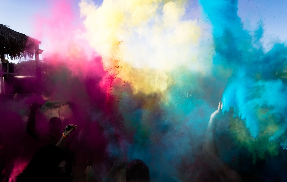 bue ,yellow, and pink powders in the air during daytime