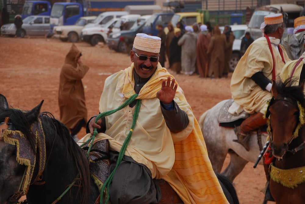 man riding black horse smiling and waving his left hand