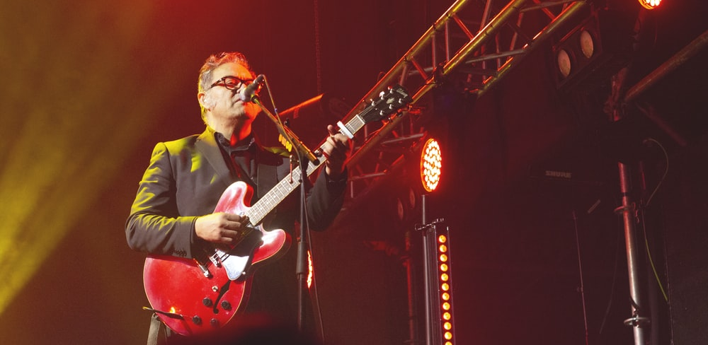 man standing and playing with red electric guitar in front of microphone