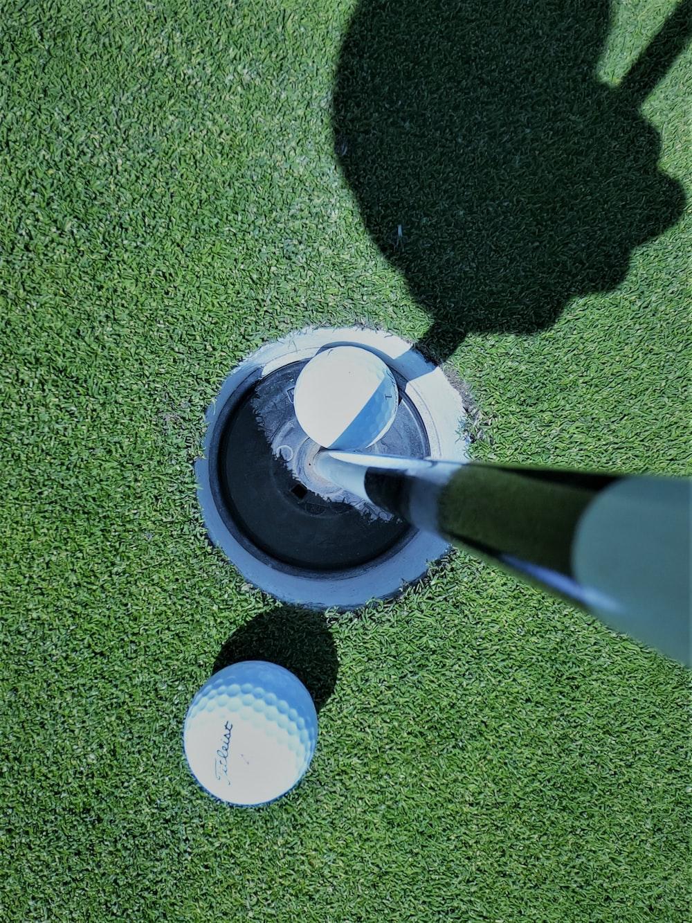 white golf ball on goal hole
