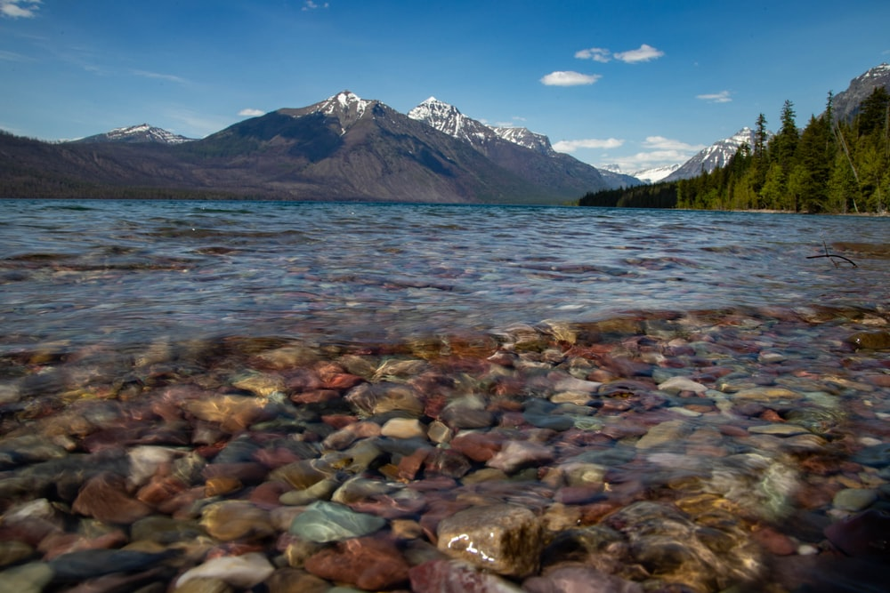 lake with rocks on shore near trees and mountains during day