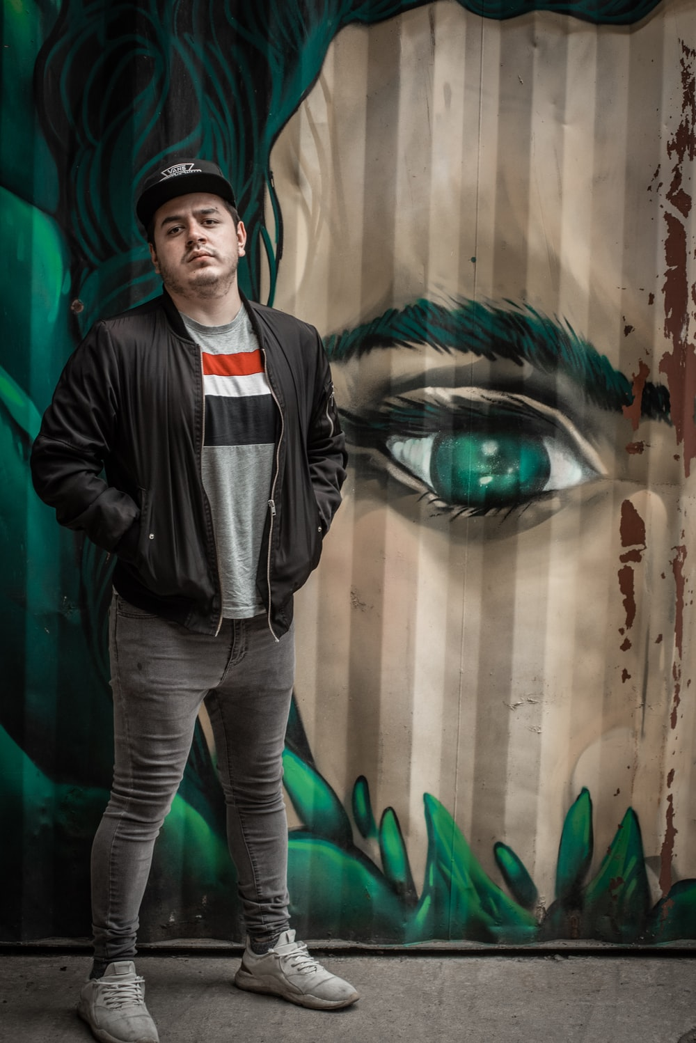 man with both hands in his jacket's pocket standing in front of wall with woman mural