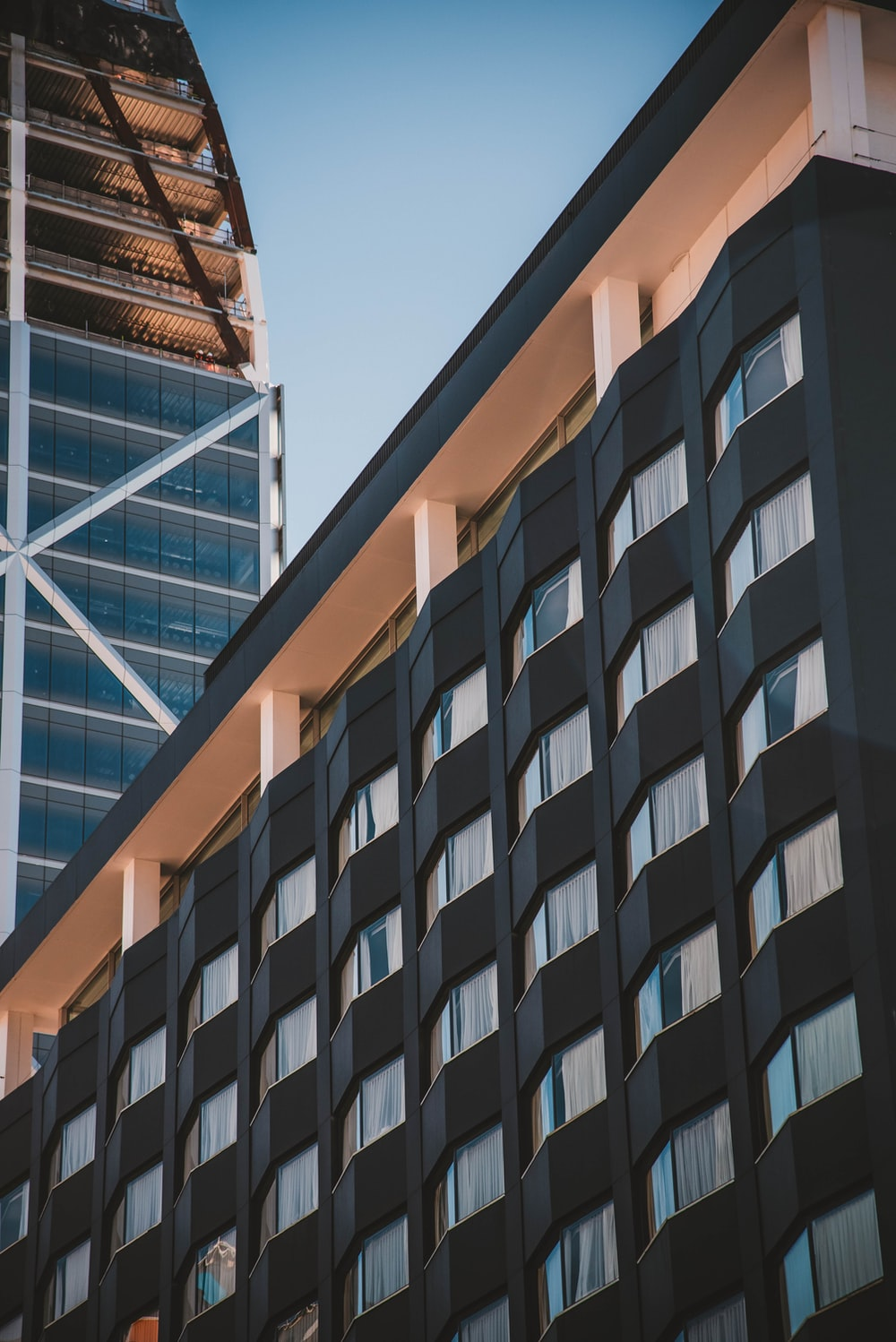 low-angle photography of black and brown high-rise building during daytime