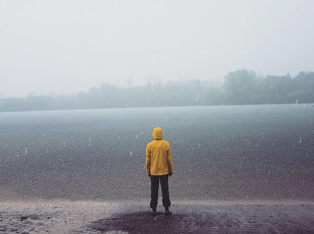 man standing at the shore facing the ocean during rain