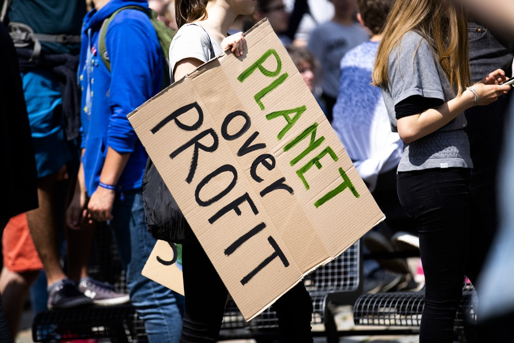 woman holding Planet over Profit placard