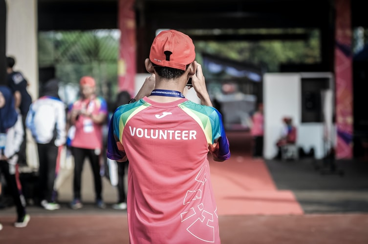 """A boy facing away from the camera with a t-shirt that says """"volunteer"""" on the back."""