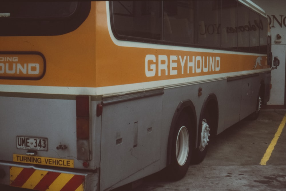 orange and grey Greyhound bus parked in building