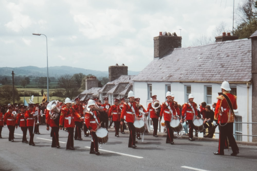 group of men in red uniform playing assorted instruments at the road