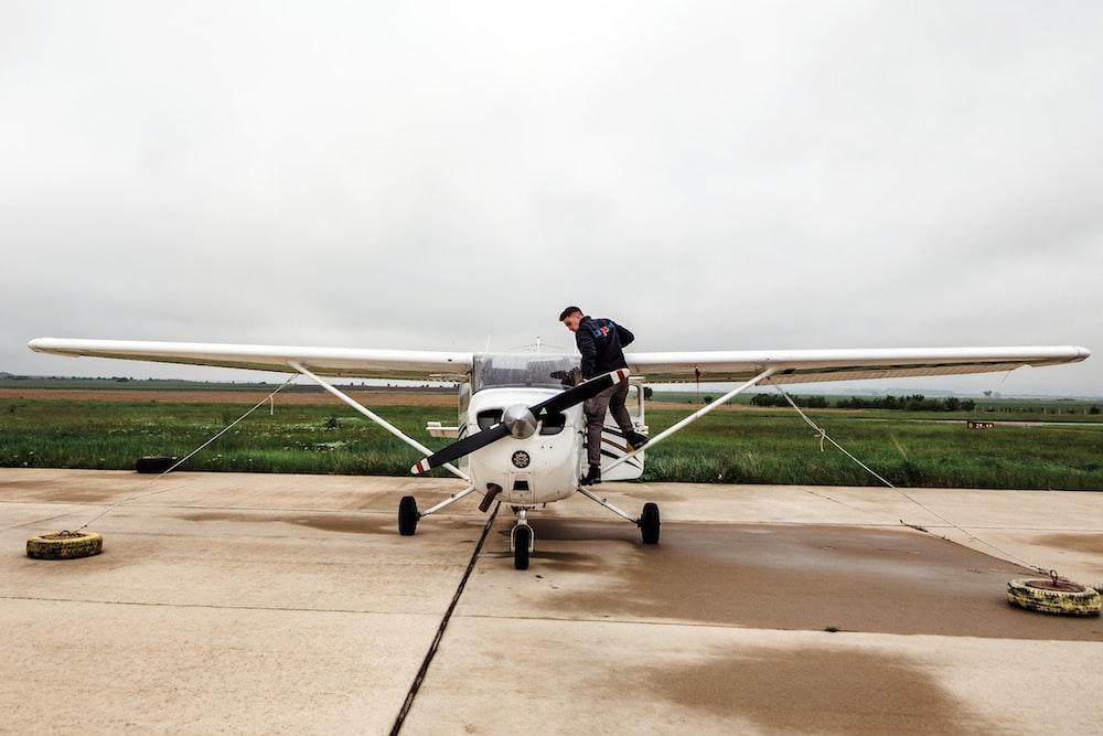 man riding white plane during daytime