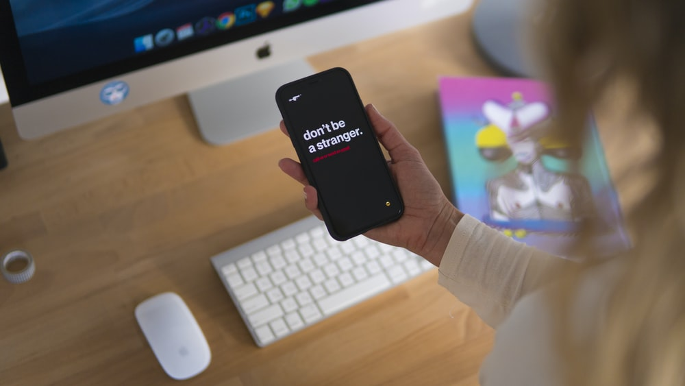 person holding black iPhone displaying don't be stranger