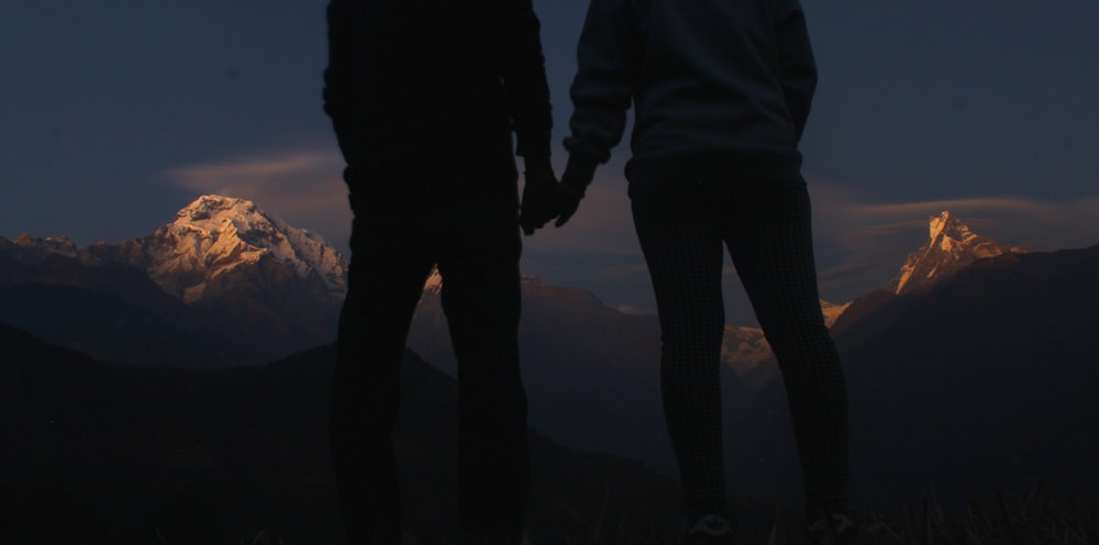 silhouette photo of two people holding hands