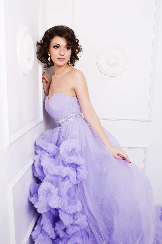 woman in purple strapless wedding dress leaning on wall